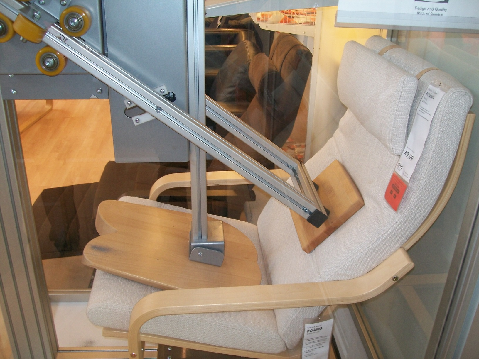 "At IKEA there are chairs like this one which are being tested by having a robot ""sit"" on them repeatedly with a robotic wooden bum. This chair was shown in a glass case for demonstration purposes, being sat on again and again for everyone's enjoyment."