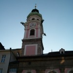 A tower, possibly part of a church with a clock with roman numerals.